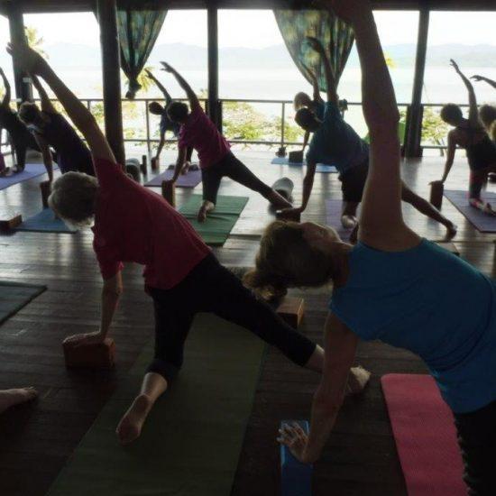 People doing yoga on a deck at Daku Resort, Savusavu