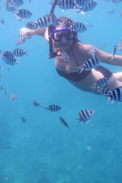 A woman snorkels with fish in Savusavu Bay.