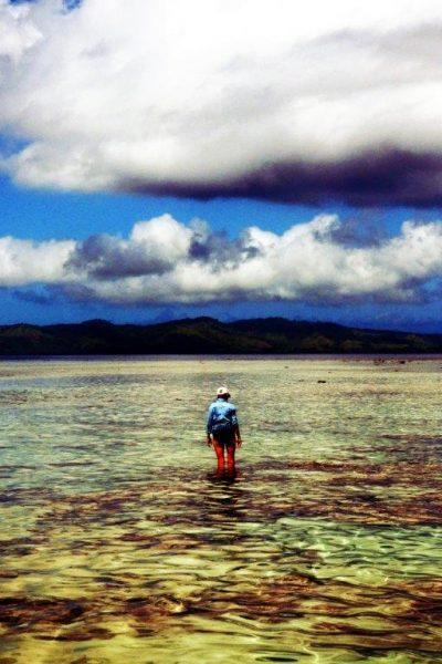 A man wades through the shallows of Natewa Bay.